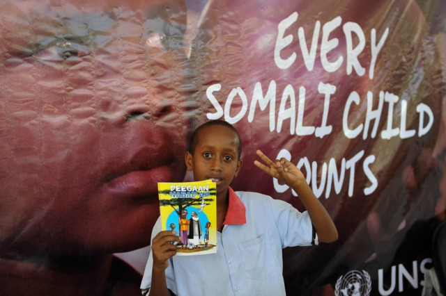 A student at the Hamar Jajab School in Mogadishu holds a peace-themed comic book for children produced by UNSOM during the commemoration of Somalia's ratification of the Convention on the Rights of the Child on 20 January 2015. UN Photo/Ilyas Ahmed