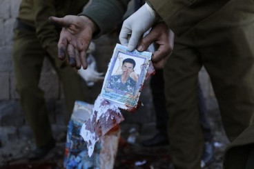 Policemen hold a photo of one of the victims of a car bomb attack outside the police college in Sanaa January 7, 2015. (c) REUTERS/Khaled Abdullah